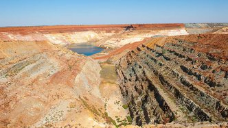 Man made deep hole for open cut mining in outback Australia, close to Meekatharra in Western Australia, panoramic view with copy space.