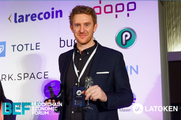 PlayChip advisor Luke Lombe with the Draper Hero's Choice Award at the Blockchain Economic Forum