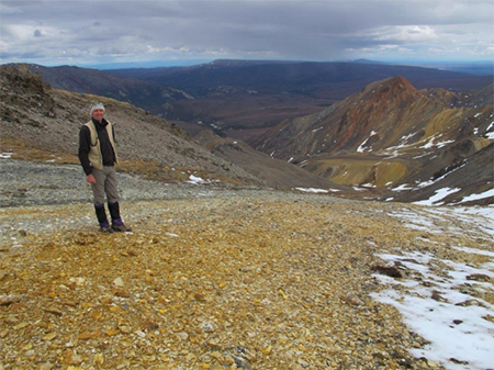 The Company's Exploration Manager at Dry Creek West looking west along strike within the footwall alteration zone, with Red Mountain in the background.